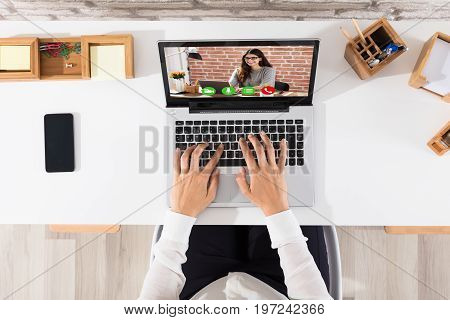 Elevated View Of Businessperson Videoconferencing With Happy Female On Laptop At Workplace