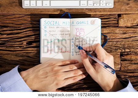 Close-up Of A Person's Hand Making Social Media Plans On Notebook Over Wooden Desk