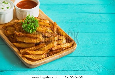 Homemade french fries serve with ketchup and sour cream or mayonnaise. Golden brown crispy french fries sprinkle with salt and oregano on wood plate for snack or appetizer. French fries on wood table. Delicious french fries on wood table.