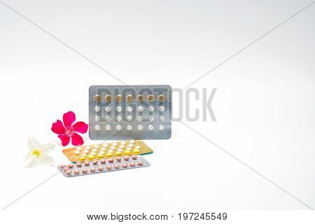 Contraceptive pills with pink and white flower on white background