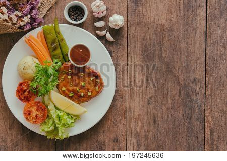 Barbecue pork steak on white plate served with barbecue sauce and vegetables. Pork steak for lunch or dinner on wood table. Moist and soft homemade pork barbecue served with mash potato and vegetable. Pork steak in top view or flat lay.