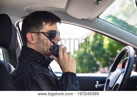 Close-up Of A Male Private Detective Sitting Inside Car Talking On Walkie Talkie