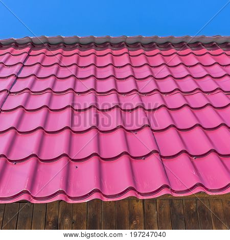 The roof of the country house is covered with metal roofing. The material for the roof