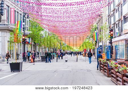 Montreal Canada - May 26 2017: People walking on Sainte Catherine street in Montreal's Gay Village in Quebec region with hanging decorations