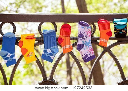 Various colorful children socks hanging on a washing line outdoors. Many little socks on a clothesline for kids - boys and girls. Happy childhood background