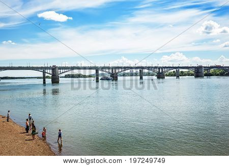 The river Ob Novosibirsk Siberia Russia - July 17 2017 October ( Utilities ) bridge campers and people on the promenade by the water