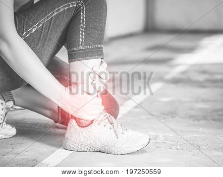 Black and white young woman suffering from an ankle injury while exercising and running. Sport excercise concept.