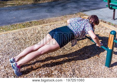 Young Woman Exercising On Push Up Bar