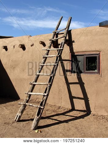 Southwestern ladder leaning against adobe wall in Taos Pueblo, New Mexico