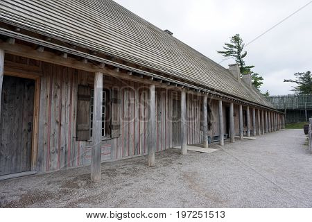 MACKINAW CITY, MICHIGAN / UNITED STATES - JUNE 18, 2017: Eaves provide shelter in front of a longhouse in Fort Michilimackinac, in the Colonial Michilimackinac State Park in Mackinaw City, Michigan.