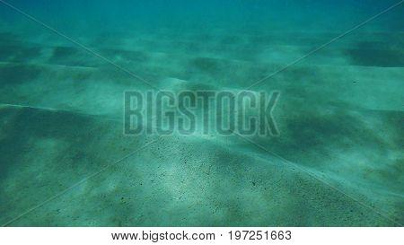 Underwater view of the sand and the sunlight. Nassau, Bahamas.