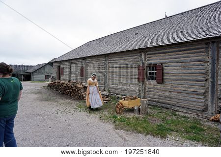 MACKINAW CITY, MICHIGAN / UNITED STATES - JUNE 18, 2017: A costumed interpreter walks toward a wheelbarrow behind a wooden building in Fort Michilimackinac, in the Colonial Michilimackinac State Park.