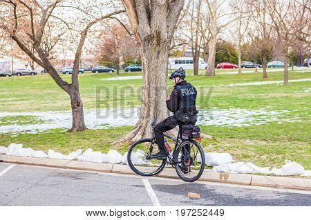 Washington Dc, Usa - March 17, 2017: Policeman On Bicycle Talking On Radio By Snow