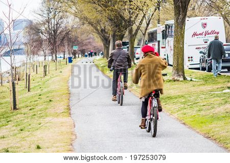 Washington Dc, Usa - March 17, 2017: Couple On Bikes Riding On Sidewalk In Spring By Potomac River T