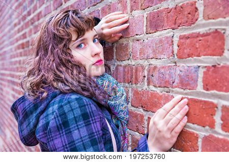 Young Woman Leaning Against Brick Wall In Coat During Winter