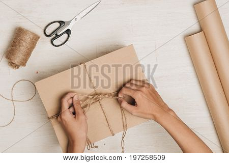 Man wrapping gift. A parcel wrapped in brown paper and tied with rough twine