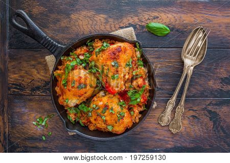 One pan tomato basil chicken and rice in a black cast-iron skillet on the wooden rustic table top view.