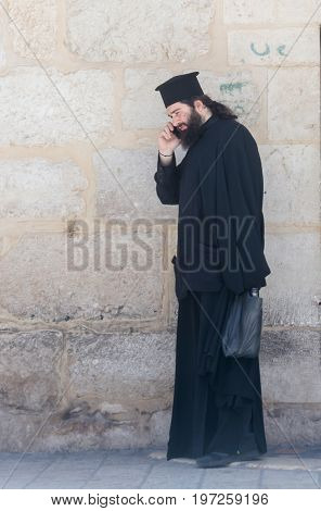 Jerusalem Israel July 14 2017 : The clergyman stands and talks on his mobile phone in the old city of Jerusalem Israel.