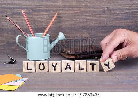 Loyalty concept.Wooden letters on dark background. Office desk