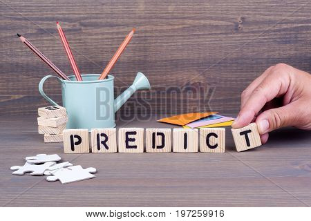 Predict concept.Wooden letters on dark background. Office desk