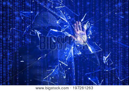 Hooded hacker smashing the screen with one hand in front of blue binary background cybersecurity concept