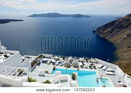 OIA GREECE - MAY 17: The tourists enjoying their vacation at luxury hotel on May 17 2014 in Oia Greece. Up to 16 mln tourists is expected to visit Greece in year 2014.