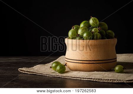 Juicy ripe berries of a gooseberry in a small wooden pot on black surface. Gooseberry harvest.