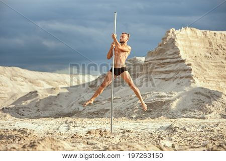 Male athlete dances on a pole among the sand in the desert.
