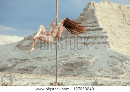 Woman acrobat dances on a pole an erotic dance.