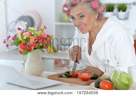 Senior woman with pink hair curlers on head sitting at table with laptop and cutting vegetables