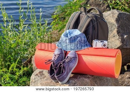 Hiking Backpack, Sneakers, Hat, Camera And Camping Mat On Rock With River Embankment Background