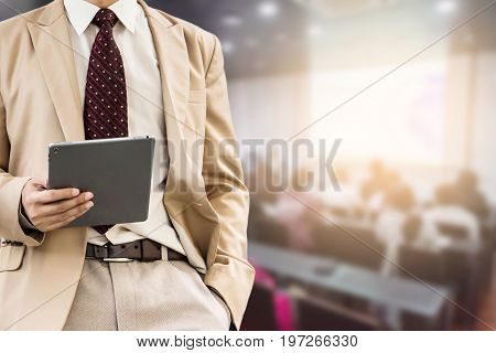 businessman using the tablet or mobile phone blurred of conference hall or seminar room with attendee background.