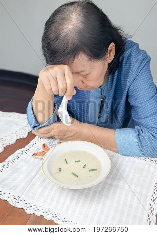 Elderly asian woman bored with food .