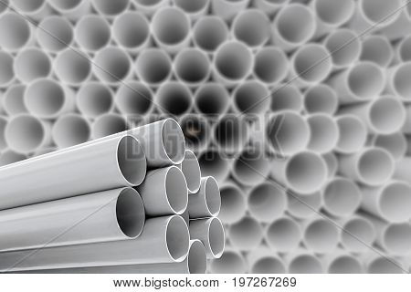 Gray PVC pipes stacked in warehouse .