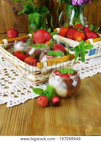 Chocolate sauce in little tasters and ripe strawberries on a wooden background
