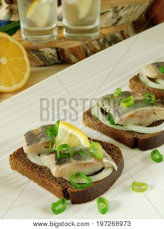 Salted herring with onion on a slice of bread and misted glass vessels filled with drink