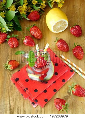 Refreshing drink with ice cubes, strawberries and mint surrounded by fresh strawberries on a wooden background. View from above