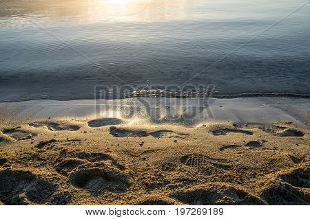 Beautiful sunrise at the clear calm sea on the water's edge there are footsteps in the wet sand