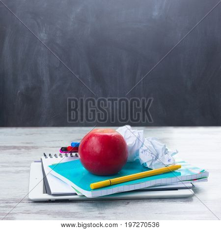 Apple with school supplies on white wooden table, empty blackboard in background