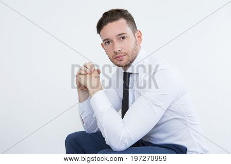Calm handsome young businessman in white shirt sitting and looking at camera opposite white wall. Serious confident male manager leaning on knees. White-collar worker concept