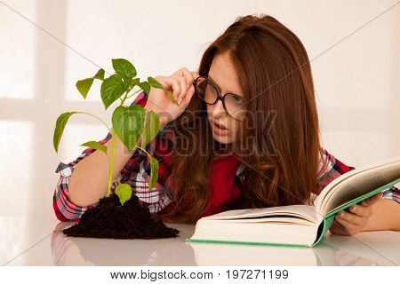 Attractive Young Botany Student With Seedlnng And Books