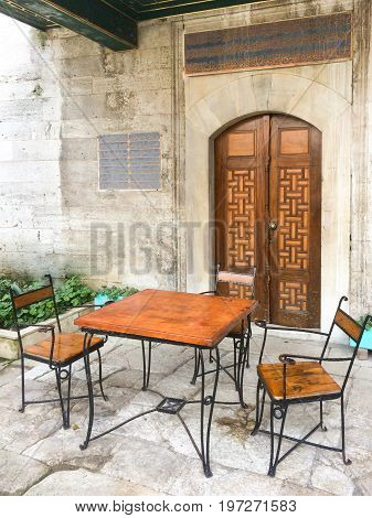 Metal And Wooden Table With Two Arabic Style Chairs In Front Of The Mosque Wooden Door