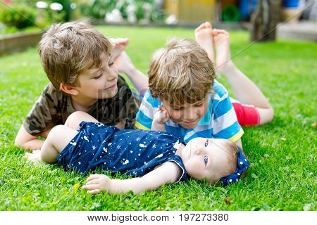Two little happy kid boys with newborn baby girl, cute sister. Siblings on grass in summer or spring in garden. Kids bonding. Family of three children
