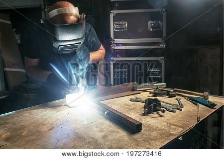 A bald strong man in a black T-shirt creates with his own hands a mettalical product and welds a metal welding machine in the production hall bright sparks fly in different directions many tools