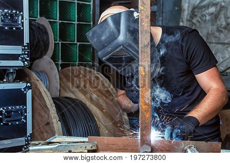 A bald strong man in a black T-shirt welds a metal welding machine in the production hall a dark background lots of smoke rises to the ceiling