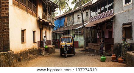 Gokarna, Karnataka, India- 29 January 2014 - yellow rickshaw and local people with jugs of water in a street