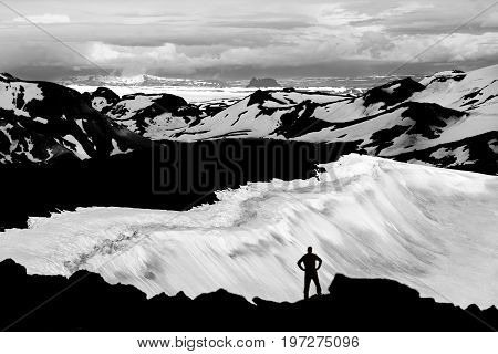 Man reaching mountain summit, watching glaciers and snowfields in Iceland. Unreal view from the volcano Ok with its snow-filled crater to the snowfields and glaciers of Thorisdalur. Large Langjokull glacier in background.