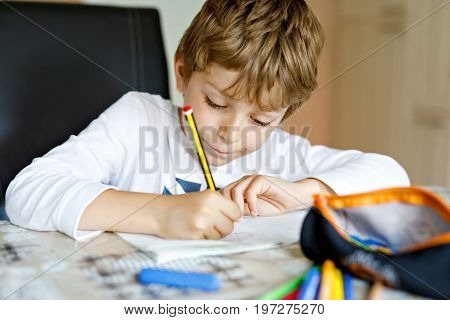 Tired little kid boy at home making homework at the morning before the school starts. Little child doing excercise, indoors. Elementary school and education
