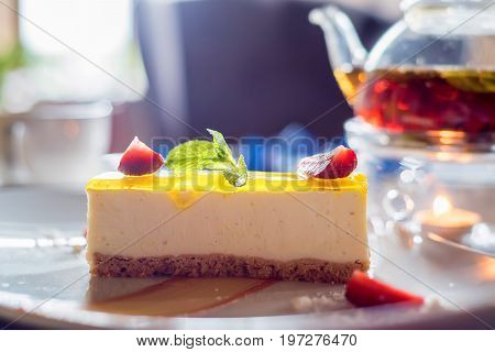 Tasty cheese cake with strawberry, mint and black tea in glass teapot