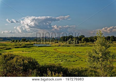 A view of the river valley with its juicy herbs and a hovering cloud.